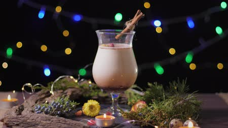 gwóżdź : homemade traditional Christmas eggnog drink in a glass with ground nutmeg and cinnamon decorating with christmas tree and lights, preparing for celebrating festive holiday season Wideo