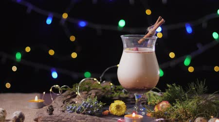 küçük hindistan cevizi : homemade traditional Christmas eggnog drink in a glass with ground nutmeg and cinnamon decorating with christmas tree and lights, preparing for celebrating festive holiday season Stok Video