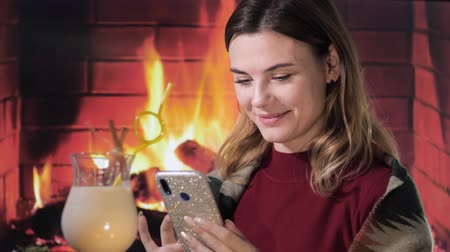 küçük hindistan cevizi : nice smiling girl sitting with a phone in her hands near Eggnog christmas cocktail on the background of fireplace, homeliness