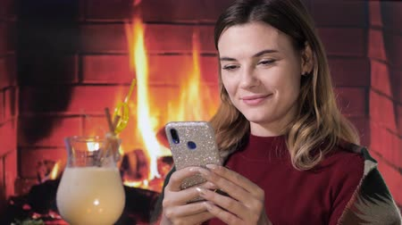 küçük hindistan cevizi : portrait of a joyful female with a smartphone in her hands sitting in a cozy atmosphere near a traditional egnog cocktail, preparing for a christmas party against a burning fireplace Stok Video