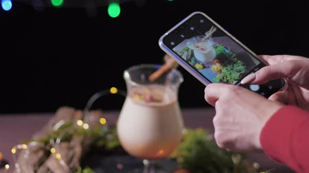 küçük hindistan cevizi : woman takes a photo on the phone of a traditional cocktail, of a cooked home for a Christmas party with friends on background of holiday decorations Stok Video