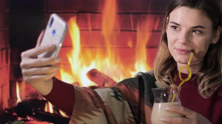 küçük hindistan cevizi : young smiling female takes selfie on smartphone with traditional a eggnog cocktail in hand on fireplace background