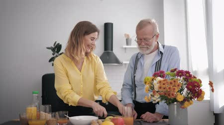 栄養満点の : caring for older generation, a cheerful smiling granddaughter with her peppy grandfather have fun talking and preparing a healthy breakfast for keeping healthy in the kitchen at the table 動画素材