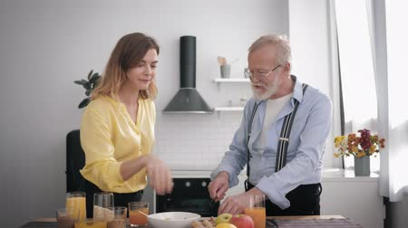 dede : cheerful sociable granddaughter cheerfully talks and drinks juice in the kitchen with her beloved grandfather in glasses for sight while making breakfast from healthy products, health care Stok Video