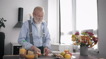 생기 : elderly attractive grandfather with a beard in glasses and takes care of his health, prepares a wholesome breakfast of fruit slices apples standing by the table