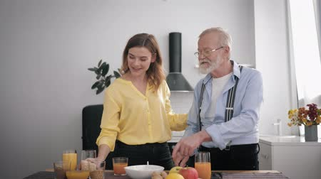 parentes : family relationship, happy peppy old man prepares a delicious breakfast in the kitchen with healthy products, mixes with his cheerful beautiful adult granddaughter at the table background of the kit