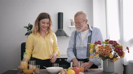 栄養満点の : family relationships, a happy smiling granddaughter is having fun with her grandfather in glasses for sight and a beard, a lover of proper nutrition, is preparing a healthy breakfast in the kitchen 動画素材