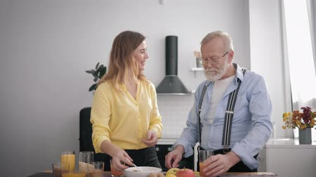 peppy : family relationships, smiling adult girl helps her old grandfather prepare vitamin salad from healthy products while having fun together in the kitchen