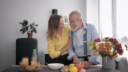 peppy : grandparent, caring grandfather with a beard and glasses for vision prepares vitamin food for himself and his smiling granddaughter standing at the table
