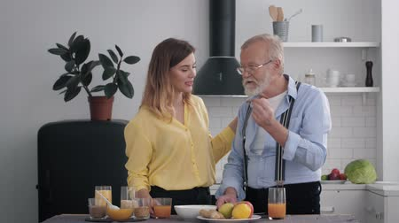peppy : happy family, cheerful grandfather and his smiling granddaughter have fun in the kitchen while making breakfast from healthy and organic products Stock Footage
