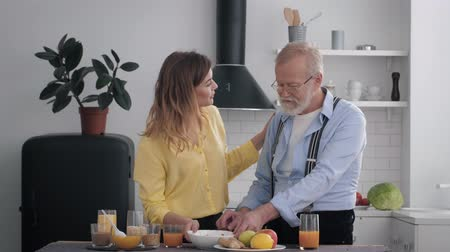 peppy : healthy food, elderly cheerful man with a cute smiling girl with a beard discussing food for breakfast drink juice standing at a table on the background of the kitchen