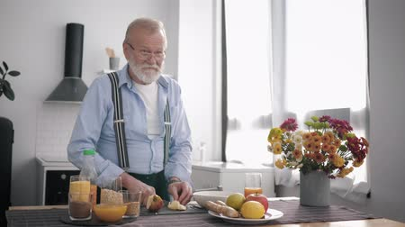peppy : old peppy man with a beard in glasses a lover of proper nutrition prepares healthy fruity salati drinks vitamin juice, while standing at the table background of a beautiful kitchen