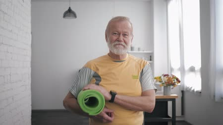 peppy : Portrait of a handsome satisfied old man in great shape with a yoga mat in his hands and a smart watch, after playing sports to maintain his health and showing a thumbs up gesture while standing indoor