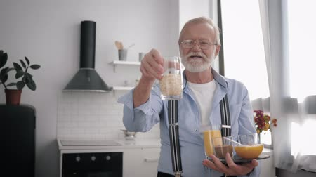 daadkracht : portrait of an attractive old man with a beard and glasses for vision, talking about useful cereals for maintaining health Stockvideo