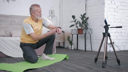 ajánlás : social media marketing, Influencers blogger old man takes a review of smart watches for vlog makes healthy lifestyle content and recommending to his audience of subscribers a device sitting on a yoga