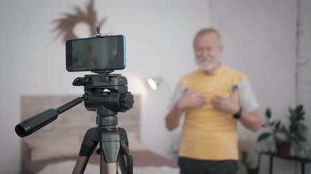 telefonia : socially active grandfather Influencers pays special attention to a healthy active lifestyle shows exercises for the subscriber recording video on the phone for his blog