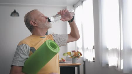 peppy : sports grandfather drinks clean water to maintain health holds a yoga mat in his hands while standing indoors with a beautiful interior