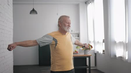physically : wellness exercises, an elderly male takes care of his health performs exercises waving his arms while standing indoors