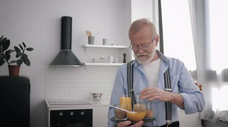 conserva : wholesome products, an elderly smiling man in glasses for vision, who cares about health, talks about cereals keeps food in his hands Stock Footage