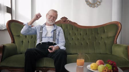 peppy : attractive elderly man with a beard in glasses for vision sits on a sofa with a TV remote control and emotionally watches a football match