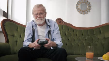 peppy : attractive old male, retiree in glasses for vision with a beard and a joystick in hands is having fun playing video games while sitting on the sofa in the room