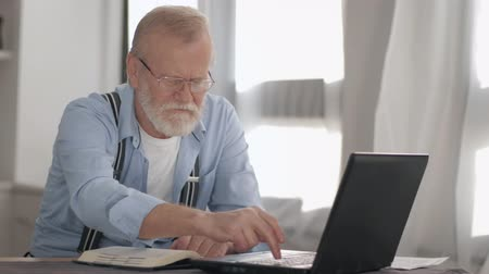 daadkracht : attractive old pensioner, old male with glasses for vision works at computer with bank accounts and payments online smiles and looks at camera