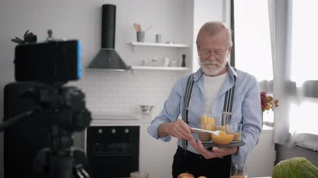 peppy : food blogger, elderly Influencers man with glasses for vision and a beard writes a blog about healthy products and removes vlogs on a smartphone while standing in the kitchen and holding organic nutriti Stock Footage
