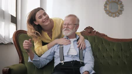 herança : friendly senior dad with gray hair and glasses for vision hug adult granddaughter, talking joking having fun enjoy time together and good relationships sit on sofa at home Stock Footage