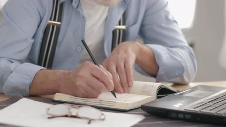 daadkracht : Close-up of male hands, holding a pen to take notes in a notebook calculating numbers on a computer while sitting at a table in a room