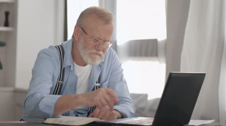 utilidade : modern age, attractive pensioner with a gray beard in glasses pays utility bills online working at computer