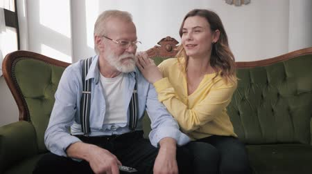 herança : old parents, a happy young daughter and a loving elderly grandfather have fun cute chatting and laughing while sitting on the couch during a family weekend Stock Footage