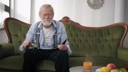 peppy : old fan, a grandfather with glasses for sight and beard with a remote control very emotionally watches sports and gestures with hands while sitting on sofa against white wall