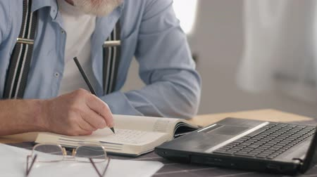 daadkracht : portrait of a modern pensioner, old male freelancer who works at a portable computer at home and writes bills to a notebook smiling and looking at the camera