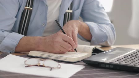 daadkracht : male hands closeup makes notes in notebook while working at a computer while sitting at table