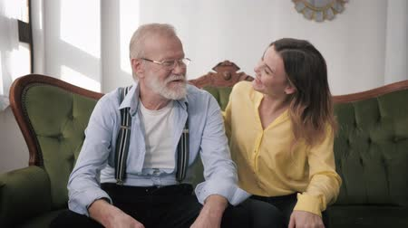 peppy : portrait of attractive grandfathers with gray hair and glasses for vision and an adult beautiful granddaughter are smiling and looking at the camera while sitting on a sofa, old parents