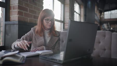 webinar : business coach, woman in glasses for vision conducts online training remotely communicating with students and making notes in a notebook while sitting at a laptop in a cafe