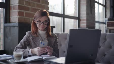 görüş uzaklığı : online business management, a modern business woman in glasses for vision works remotely at a computer and checks reports on a smartphone while sitting in a cafe, useful gadgets Stok Video