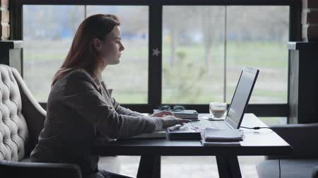 unlucky : problems in business, a young sad business woman is upset because of problems and poor financial reporting, fists on the table and closes laptop cover while working remotely with online bookkeeping while sitting in a wifi cafe Stock Footage