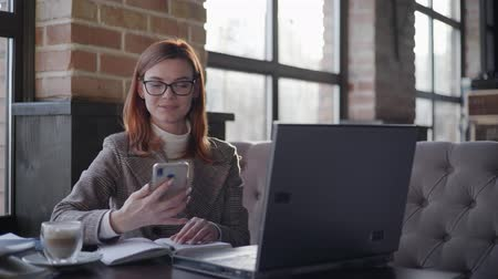 görüş uzaklığı : small business owner modern woman entrepreneur with glasses for vision working online behind a laptop checking reports on smartphone sitting in cafe wifi