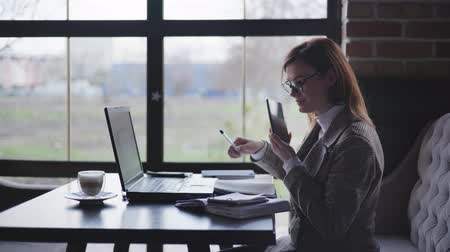 görüş uzaklığı : successful business woman, female with glasses for vision works at the computer and smartphones happy because of receiving good news shows a yes sign, concept of achievement