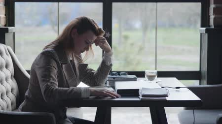 unlucky : young sad girl is sitting upset because of the chopping block of work and accounting problems in business, holds her head with her hand while writing in a notebook while sitting at a table in a cafe against the window