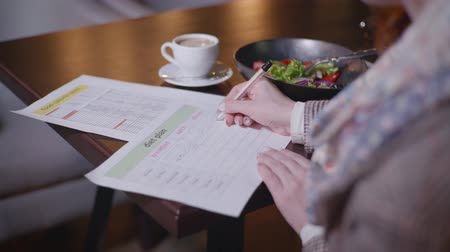 dietético : body care, a young woman watching her figure counts calories in a vegetarian salad of fresh vegetables and writes in a diet plan, healthy eating concept Stock Footage