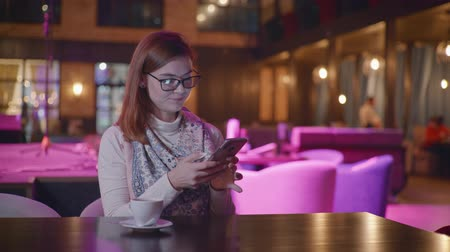 karczma : portrait of beautiful smiling girl with glasses using smartphone chatting with friends on social networks, woman drinking coffee while relaxing in an expensive presentable restaurant