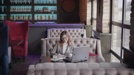webinar : successful businesswoman in glasses drinks coffee in restaurant working on laptop computer and smartphone, enjoys working online sitting at table by window, modern work