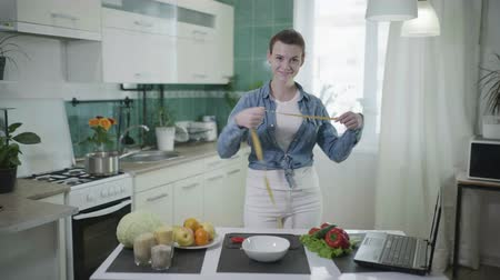ネットブック : good diet, young happy woman standing in kitchen near table with healthy food measures her waist with a tape measure after successful weight loss program