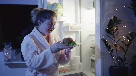 полночь : night hunger, a young girl in a dressing gown in the kitchen opens the fridge and eagerly bites a burger then go away in room with a plate in his hands