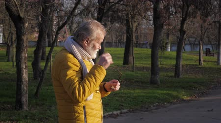 jeuk : mature man rubbing his eyes because he feels some itchiness due to allergy or infection while walking in a city park