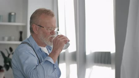 лучше : sick mature man with a gray beard retirement takes a pill with water for health and feels better at home near window