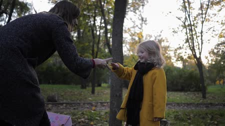 prole : playing with a child, mom with a smiling girl have fun playing paper scissors in a stone for a walk in the autumn park Stock Footage