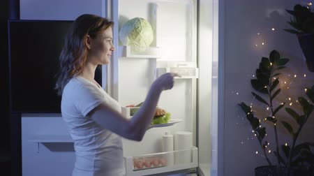 dietético : fast food, a beautiful girl a poor diet, eats harmful meat at night takes sweets from the refrigerator and leaves with them, proper nutrition Stock Footage